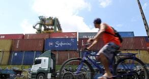 Un trabajador portuario pasa frente a unos contenedores en Santos, Brasil, feb 22 2013. El déficit de cuenta corriente de Brasil se redujo en febrero debido a la depreciación del real brasileño y a que se mantiene un estancamiento en el crecimiento económico, mostraron datos del banco central el martes.  REUTERS/Paulo Whitaker