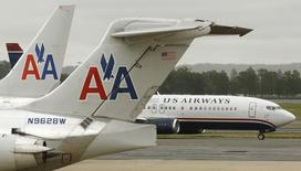 A US Airways plane passes American Airlines planes at Ronald Reagan National Airport in Washington April 23, 2012.   REUTERS/Kevin Lamarque