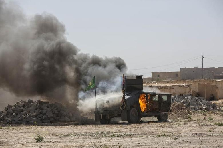 A military vehicle, belonging to Shi'ite fighters known as Hashid Shaabi, burns after being hit by Islamic State militants, during clashes in northern Tikrit, March 11, 2015.  REUTERS/Stringer