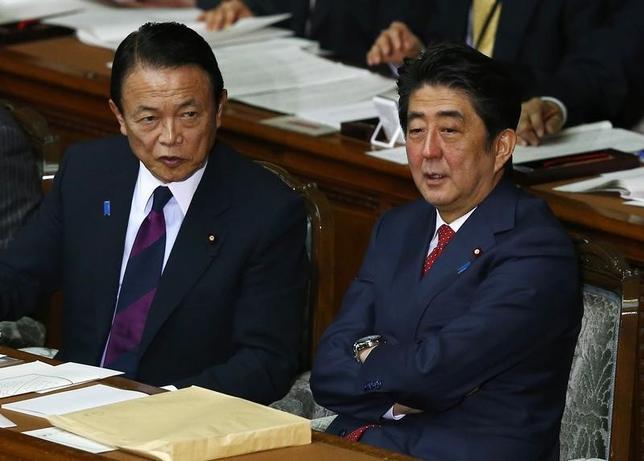 3月24日、アジアインフラ投資銀行(AIIB)への参加をめぐって、日本政府が難しい立場に置かれている。写真は安倍首相(右)と麻生財務相。2月撮影(2015年 ロイター/Takaki Yajima/Pool)