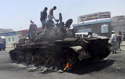 People stand on a tank that was burnt during clashes on a street in Yemen's southern port city of Aden March 29, 2015. REUTERS/Stringer