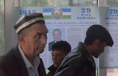 Люди у предвыборного плаката Ислама Каримова в Ташкенте. 26 марта 2015 года. Жители Узбекистана вышли в воскресенье на президентские выборы, итог которых в последние 25 лет всегда предопределялся в пользу действующего главы государства. REUTERS/Stringer