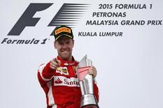 Formula One - F1 - Malaysian Grand Prix 2015 - Sepang International Circuit, Kuala Lumpur, Malaysia - 29/3/15. Ferrari's Sebastian Vettel celebrates winning the Malaysian Grand Prix with the trophy on the podium. Reuters / Olivia Harris