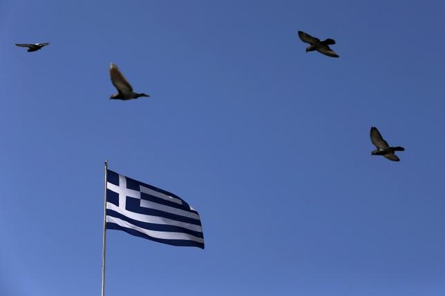 Pigeons fly over a fluttering Greek national flag in Athens March 30, 2015.   REUTERS/Alkis Konstantinidis
