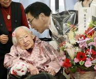Japanese Misao Okawa, the world's oldest living person, celebrates with Takehiro Ogura (R), mayor of Osaka's Higashi-Sumiyoshi Ward, on the eve of her 117th birthday at an elder care facility in Osaka, western Japan in this file photo taken by Kyodo March 5, 2015.  REUTERS/Kyodo/Files