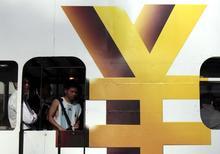 图为香港一辆电车上的男子站在人民币货币符号旁。REUTERS/Tyrone Siu