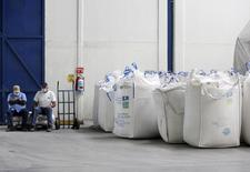 Workers sit next to bags containing sugar at the San Francisco Ameca sugar factory in the town of Ameca, Jalisco, February 18, 2011. REUTERS/Alejandro Acosta/Files