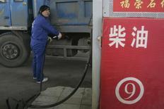 Женщина заправляет грузовик на АЗС в Тайюане. 5 ноября 2010 года. Саудовская Аравия, крупнейший в мире экспортер нефти, повысила официальные цены продажи на майские партии для Азии. REUTERS/Stringer