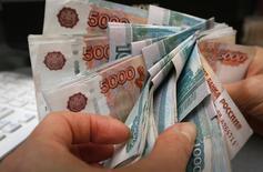 Работник красноярского магазина считает деньги. 26 декабря 2014 года. Рубль подорожал на торгах понедельника вслед за отскоком вверх нефтяных котировок в условиях неактивного и малоликвидного рынка, во многом из-за отсутствия европейских инвесторов и игроков, продолжающих праздновать западную Пасху. REUTERS/Ilya Naymushin