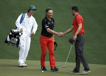 Bernhard Langer of Germany (C) shakes hands with fellow countryman Martin Kaymer as they meet on the tenth green during their practice round ahead of the 2015 Masters at the Augusta National Golf Course in Augusta, Georgia April 6, 2015.  REUTERS/Phil Noble