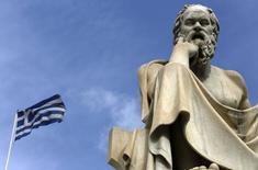 Флаг Греции и статуя Сократа в Афинах. 18 марта 2015 года. Министр финансов РФ Антон Силуанов сказал во вторник, что Греция пока не просила Россию о кредите. REUTERS/Yannis Behrakis