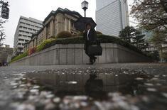 Мужчина проходит мимо здания Банка Японии в Токио 8 апреля 2015 года. Банк Японии в среду оставил без изменений свою масштабную  программу стимулов, проигнорировав отсутствие инфляции, через два года после того, как пообещал покончить с многолетним падением цен. REUTERS/Yuya Shino