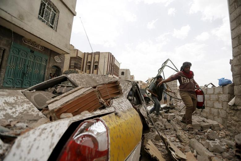 People walk past a car damaged by an airstrike in Sanaa April 8, 2015. REUTERS/Khaled Abdullah