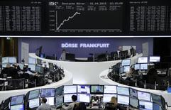 Traders are pictured at their desks in front of the DAX board at the Frankfurt stock exchange April 1, 2015. REUTERS/remote/Pawel Kopczynski