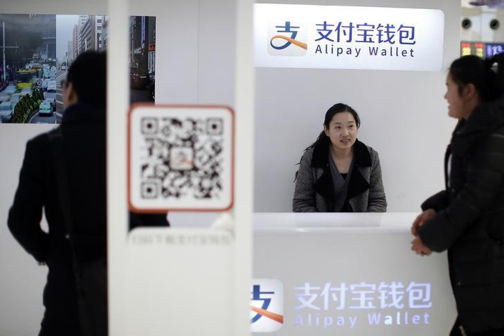 A sales assistant sits behind and under Alipay logos at a train station in Shanghai, February 9, 2015. REUTERS/Aly Song