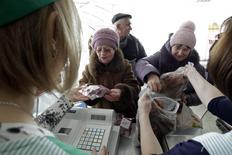 """Люди делают покупке в магазине колхоза """"Россия"""" в станице Григорополисская 17 февраля 2015 года. Две трети россиян к марту осознали, что падение рубля в прошлом году более чем на 40 процентов отрицательно сказалось на их уровне жизни, снизили аппетиты на покупки и потеряли веру в сбережения, следует из отчета об инфляционных ожиданиях и потребительских настроениях, опубликованного Банком России. REUTERS/Eduard Korniyenko"""