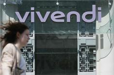 A woman walks walk past the main entrance of the entertainment-to-telecoms conglomerate Vivendi's headquarters in Paris April 8, 2015.REUTERS/Gonzalo Fuentes