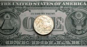 Австралийский доллар на фоне американского в Сиднее 27 июля 2011 года. Австралийский доллар упал после сообщения о резком сокращении китайского экспорта, а фунт стерлингов снизился до пятилетнего минимума к доллару США. REUTERS/Tim Wimborne