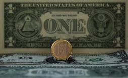 Монета в один евро на фоне долларовой купюры в Мадриде 17 ноября 2011 года. Евро снизился в понедельник, достигнув минимального значения за четыре недели, а доллар продолжает расти на ожиданиях, что ФРС США повысит ключевую ставку в ближайшие месяцы. REUTERS/Sergio Perez