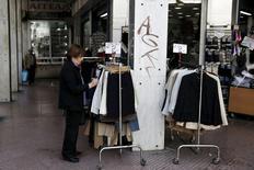 Женщина у магазина одежды в Афинах. 14 апреля 2015 года. Мировая торговля товарами вырастет на 3,3 процента в этом году и на 4,0 процента в 2016 году, то есть меньше, чем ожидалось ранее, в основном из-за слабого экономического роста, сообщила во вторник Всемирная торговая организация. REUTERS/Alkis Konstantinidis