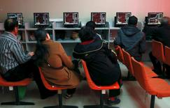 Investors look at computer screens showing stock information at a brokerage house in Shenyang, Liaoning province, April 13, 2015. REUTERS/Stringer