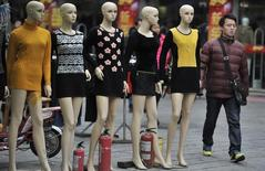A man walks past mannequins at a wholesale market in Hefei, Anhui province, February 9, 2014. REUTERS/Stringer