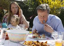 Britain's Prime Minister David Cameron of lunch with Lilli Docherty and her daughter Dakota in the garden with people who have benefited from tax and pension changes that came into force today, near Poole, south west England, Monday, April 6, 2015. REUTERS/Kirsty Wigglesworth/Pool