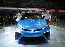 A model poses next to a Toyota Motor's concept car FCV as a worker wipes the car at the Seoul Motor Show 2015 in Goyang April 3, 2015.  REUTERS/Kim Hong-Ji