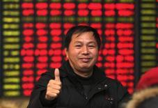 Инвестор в брокерской конторе в Наньтуне. 4 декабря 2014 года. Азиатские фондовые рынки выросли в четверг благодаря повышению цен на нефть и местным новостям. REUTERS/China Daily