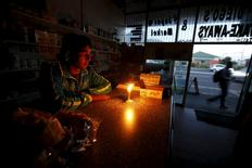 A shopkeeper waits for customers in his candlelit  fast food store during a load shedding electricity blackout in Cape Town April 15, 2015.   REUTERS/Mike Hutchings