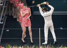 Mercedes Formula One driver Lewis Hamilton of Britain sprays champagne at a grid girl as he celebrates his victory on the podium after the Chinese F1 Grand Prix at the Shanghai International Circuit, April 12, 2015. REUTERS/Carlos Barria