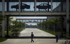 Employees walk under a car assembly line at Geely Automobile Corporation in Cixi, Zhejiang province in this June 21, 2012 file photo. REUTERS/Carlos Barria/Files
