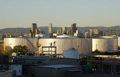 Oil storage tanks are seen at sunrise with the Rocky Mountains and the Denver downtown skyline in the background October 14, 2014.  REUTERS/Rick Wilking