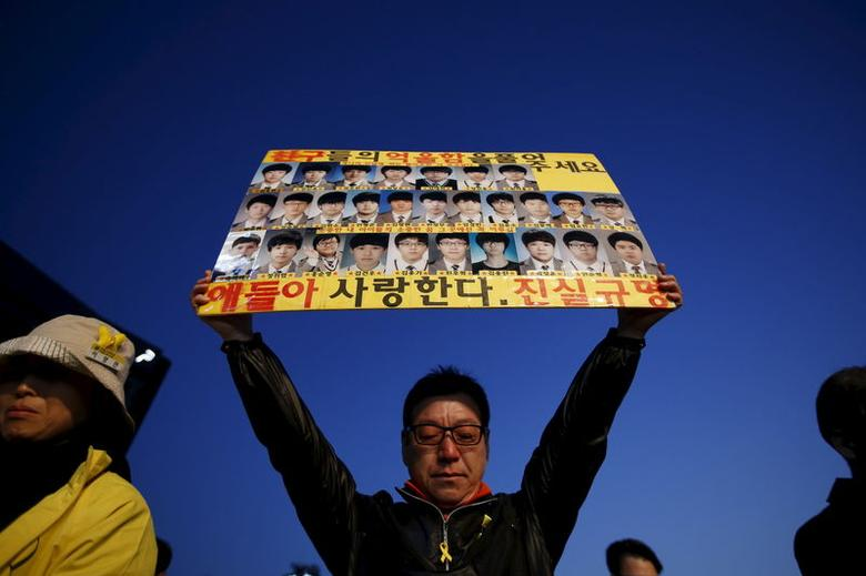 A mourner holds up a banner depicting students who died in sunken ferry Sewol during a rally to commemorate the first anniversary of the Sewol ferry disaster that killed more than 300 passengers, in central Seoul April 16, 2015. REUTERS/Kim Hong-Ji