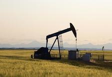 Una unidad de bombeo de crudo funcionando cerca de Calgary, Canadá, jul 21 2014. Los precios del crudo subían el lunes en una volátil sesión de operaciones, por las tensiones en Oriente Medio y el descenso del número de plataformas petroleras en Estados Unidos, que compensaron los comentarios del ministro de Petróleo de Arabia Saudita, quien aseguró que la producción de su país se mantendrá cerca de niveles récord en abril. REUTERS/Todd Korol