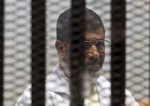 """Экс-президент Египта Мохаммед Мурси за решеткой в зале суда в Каире. 29 декабря 2014 года. Лидер движения """"Братья-мусульмане"""" Мохаммед Мурси во вторник получил двадцатилетний тюремный срок по обвинению, связанному с убийством демонстрантов, спустя примерно три года после того, как стал первым свободно избранным президентом Египта. REUTERS/Asmaa Waguih"""