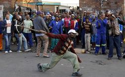 """Участники антииммигрантских волнений в Йоханнесбурге 17 апреля 2015 года. Власти ЮАР во вторник отправили армейские части во """"взрывоопасные районы"""", чтобы остановить насилие в отношении иммигрантов, которое унесло в апреле как минимум семь жизней, сообщил министр обороны. REUTERS/Siphiwe Sibeko"""