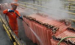 Un trabajador limpia cátodos de cobre en la refinería Ventanas de la estatal Codelco en Ventanas, Chile, ene 6 2015. La mina de cobre Salvador, la división más pequeña de la chilena Codelco, retomaba sus operaciones de manera gradual tras las fuertes lluvias y aluviones que azotaron hace unas semanas el norte del país, dijo el martes la minera estatal.  REUTERS/Rodrigo Garrido