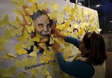 Mulher cola adesivo amarelo em cartaz de homenagem a Gabriel García Márquez na Cidade do México. 17/04/2015 REUTERS/Henry Romero