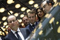 Le ministre de l'Economie, Emmanuel Macron (au centre) à côté de François Hollande), a écrit au PDG de Renault, Carlos Ghosn (à droite), pour défendre la décision de l'Etat sur les droits de vote doubles et assurer qu'elle ne met pas en danger l'alliance entre Renault et Nissan. /Photo pris ele 3 octobre 2014/REUTERS/Ian Langsdon/Pool