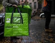 A woman holds an Amazon Fresh delivery bag in Brooklyn, New York October 23, 2014. REUTERS/Brendan McDermid