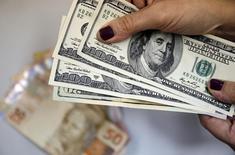 Mulher segura notas de dólar norte-americano, com notas de real ao fundo, no Rio de Janeiro. 31/03/2015 REUTERS/Sergio Moraes