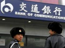 Security guards stand outside a branch of the Bank of Communications located in central Beijing in this March 30, 2010 file photo.  REUTERS/David Gray