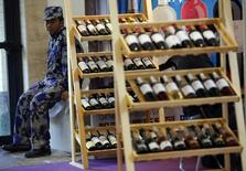 A security guard sits next to wine racks at Wine China Expo 2013 in Beijing September 24, 2013. REUTERS/Kim Kyung-Hoon