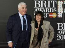 Mitch and Janis Winehouse, the father and mother of the late singer Amy Winehouse, pose for photographers as they arrive for the BRIT Awards at the O2 Arena in London February 20, 2013. REUTERS/Luke Macgregor