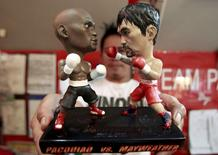 A store employee holds up a stand with miniature figurines of boxers Manny Pacquiao (R) of the Philippines and Floyd Mayweather Jr. of the U.S., at a mall in Manila April 23, 2015. REUTERS/Romeo Ranoco