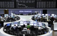 Traders are pictured at their desks in front of the DAX board at the Frankfurt stock exchange, Germany, April 28, 2015.     REUTERS/Remote/Staff