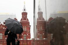 Мужчина под дождем рядом с Красной площадью в Москве 18 мая 2011 года.  Длинные праздничные выходные в Москве будут тёплыми, но дождливыми, свидетельствует усреднённый прогноз, составленный на основании данных Гидрометцентра России, сайтов intellicast.com и gismeteo.ru. REUTERS/Denis Sinyakov
