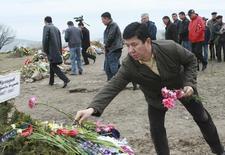 Темир Сариев, вице-премьер во временном правительстве Киргизии, возлагает цветы на могилу погибшего в ходе антиправительственных выступлений на кладбище в поселке Чон-Арык. 18 апреля 2010 года. Парламент Киргизии в четверг одобрил кандидатуру экс-министра экономики Темира Сариева на пост премьера, опустевший после того, как предшественник подал в отставку из-за спора с канадской Centerra Gold по поводу крупнейшего золотого месторождения. REUTERS/Vladimir Pirogov