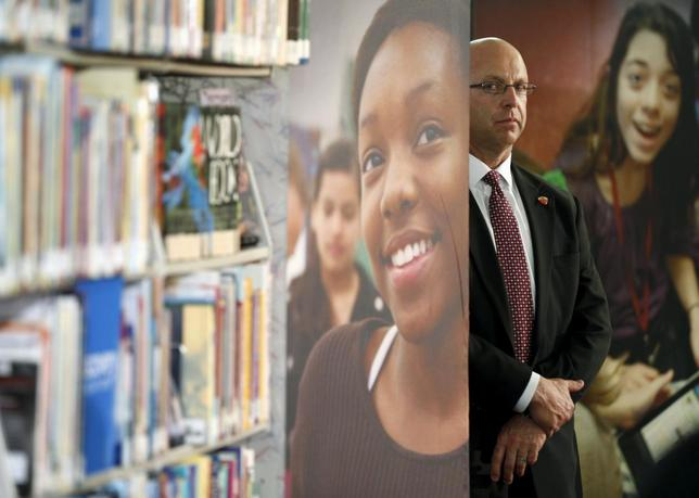 A Secret Service agent keeps watch as U.S. President Barack Obama speaks during a visit to Anacostia Library to participate in a live ''virtual field trip'' with middle school students in Washington April 30, 2015. REUTERS/Kevin Lamarque